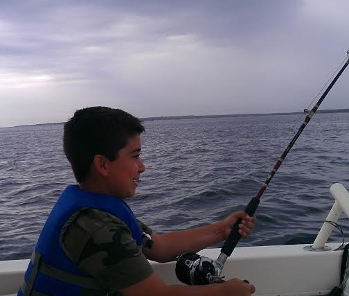 boy holding fishing pole and sitting in a boat beneath storm clouds
