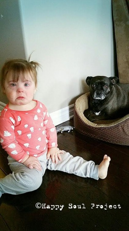 Baby looks sad while sitting next to dog that looks sad on floor