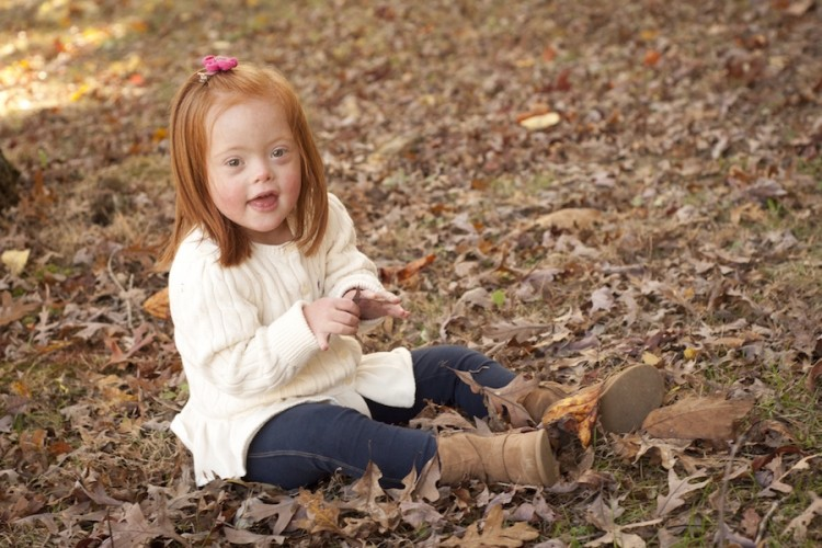 Girl sitting on the grass with fall leaves