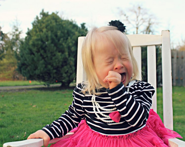Little girl crying while sitting in white chair in backyard