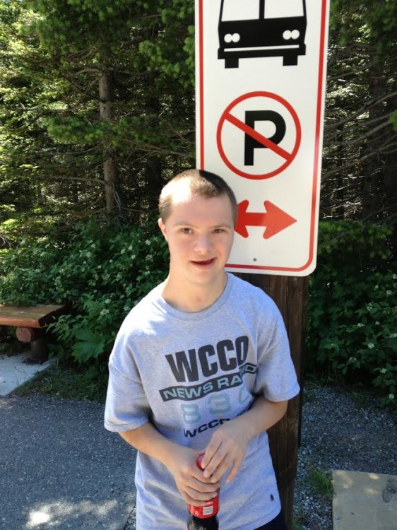 Boy holding soda bottle next to no-parking sign