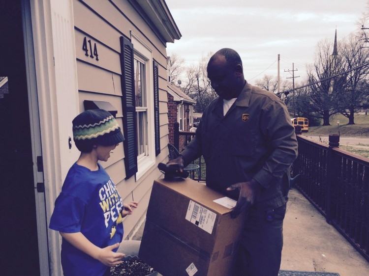 ups delivery man handing package to young boy