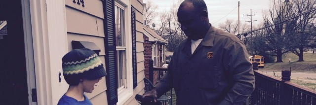 ups delivery man hands a package to a young boy