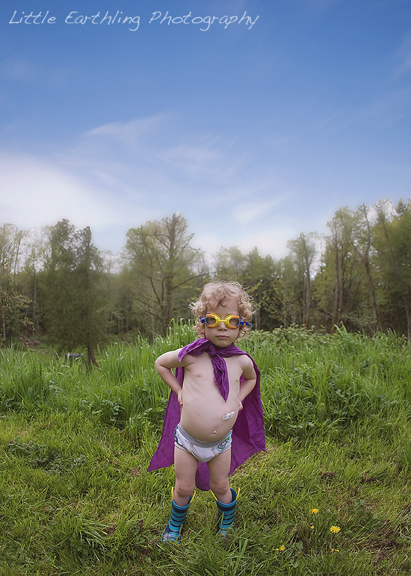 Apollo wearing purple cape and goggles, standing on the grass with trees in the background