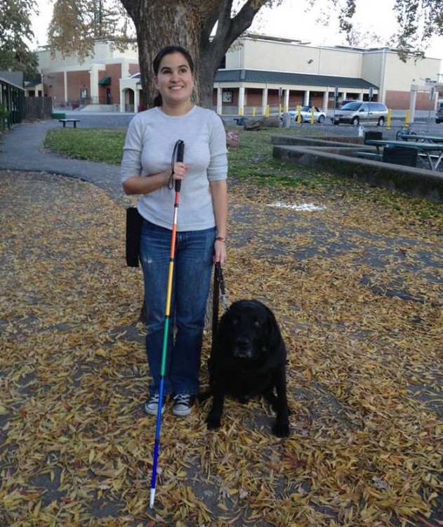 woman with her retired guide dog and rainbow cane