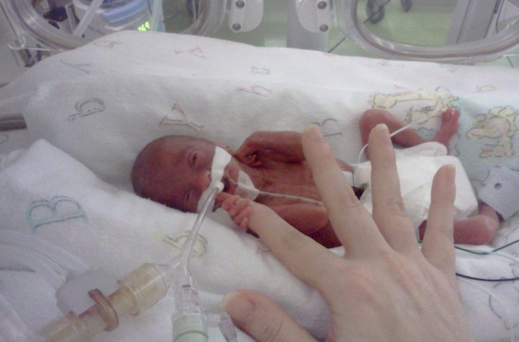 preemie baby holding an adult finger
