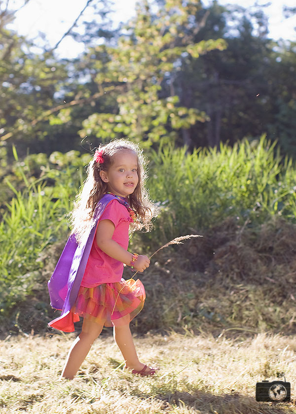 Mila walking in grassy field with a purple cape