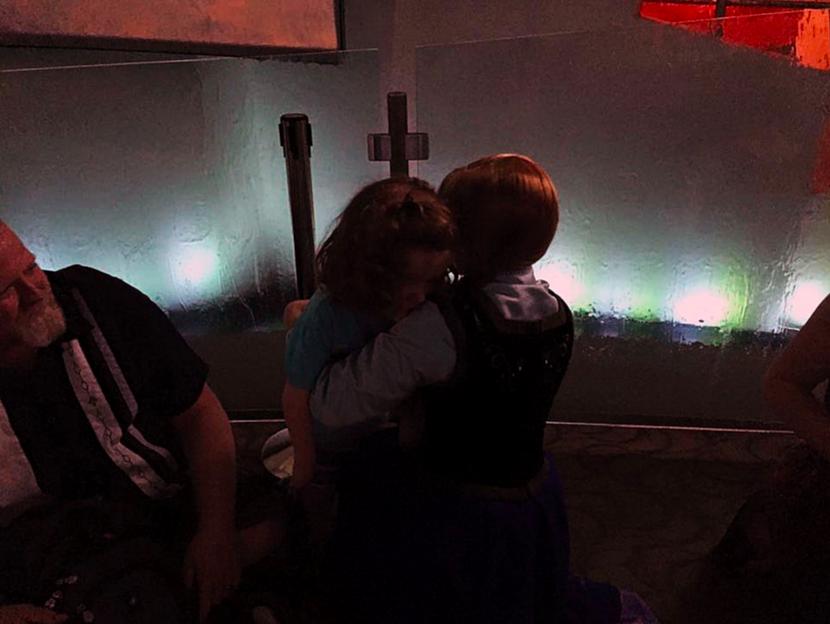 young girl hugging disneyland character