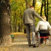 Man and woman in a wheelchair in a park during the fall