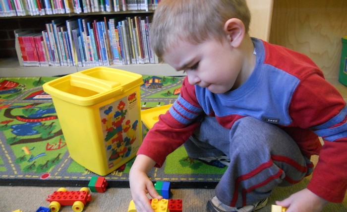 Little boy playing with a boy truck in the library