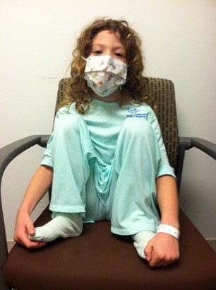 little girl with hospital mask on