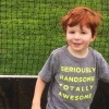 "a red-headed small boy wearing a t-shirt that says, ""Seriously Handsome. Totally Awesome,"" while standing in front of a soccer net"