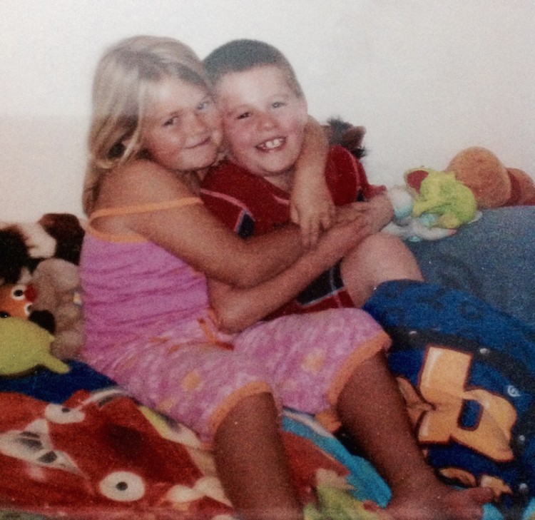 young girl hugging her brother and sitting with blankets and stuffed animals