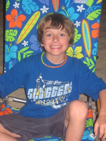 Boy sitting in a floral-print chair wearing a blue t-shirt
