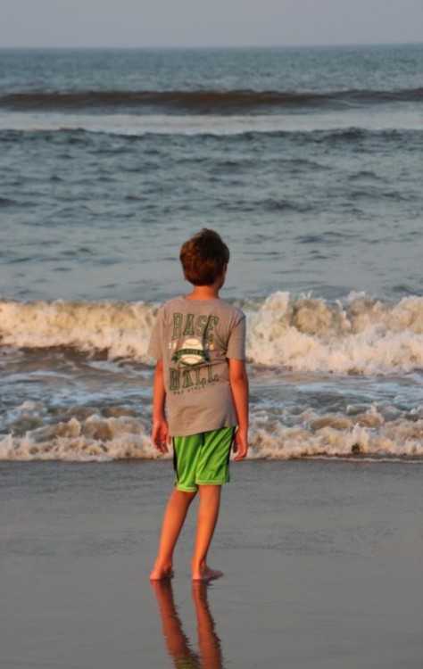Boy in t-shirt and shorts standing near beach shore