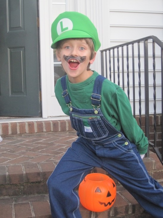 Boy wearing Luigi costume on steps of house in front of a pumpkin pail
