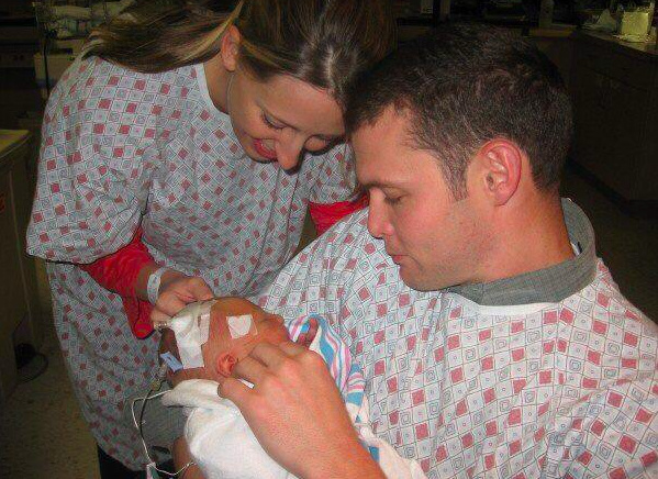 mom and dad holding newborn