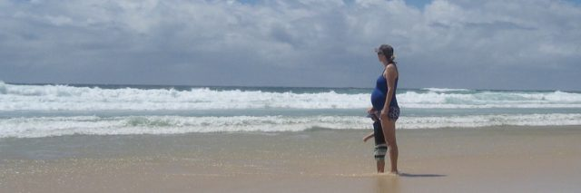 woman and small child standing on beach