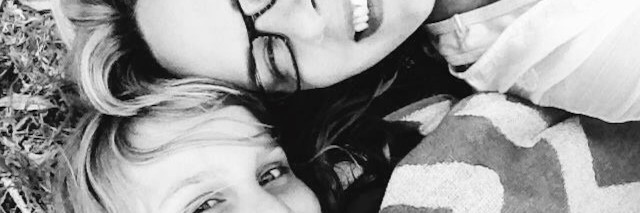 A smiling mom and daughter laying down