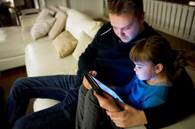 father and daughter sitting on couch and looking at ipad