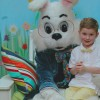 a boy sits on the lap of a person dressed in a bunny costume