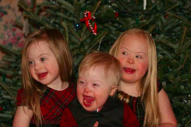 three kids with down syndrome at christmas