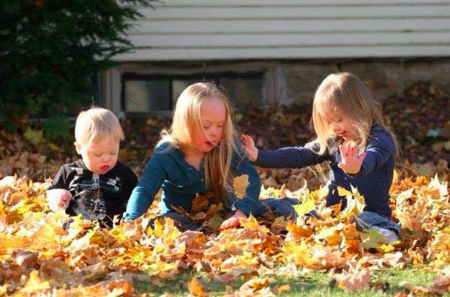 three kids playing in fall leaves
