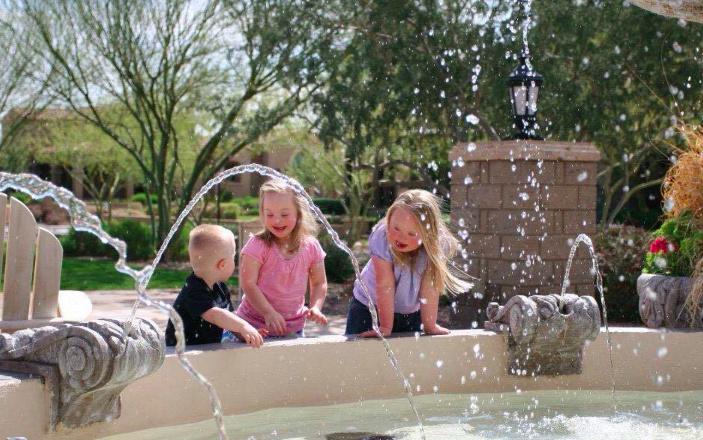 three kids playing near fountain