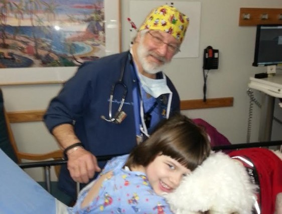 Doctor stands behind girl hugging her dog on hospital bed