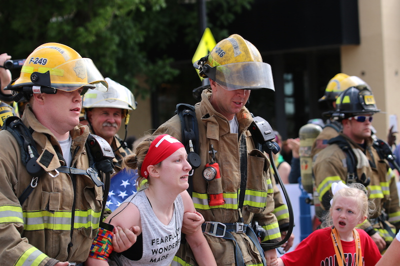 firefighters help kayley cross the finish line