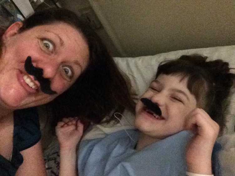 A mother and son pose in the hospital wearing fake mustaches.
