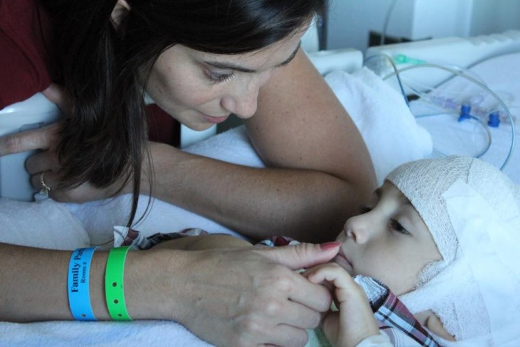 A mom gently puts her thumb on the mouth of a little boy, who's laying in a hospital bed.