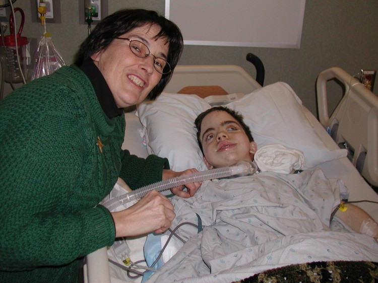 A woman smiles next to her son, who lays in a hospital bed.