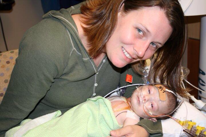 A woman holding a baby in a hospital.