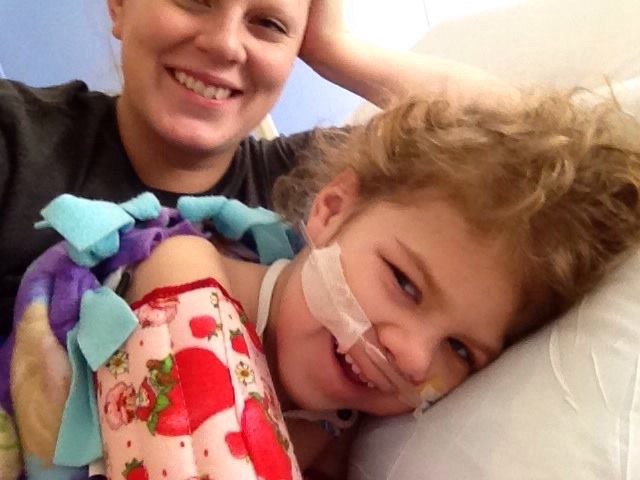 A mom smiles with her daughter, who's laying in bed with a breathing tube.