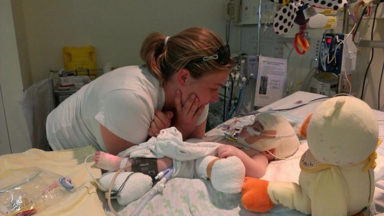 A mom stands over a little boy, who's laying in a hospital bed.