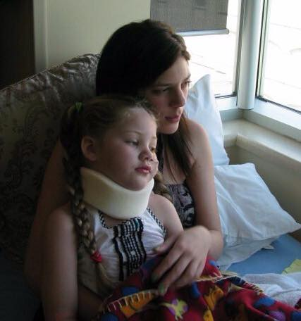 A little girl sits on her mom's lap. The girl wears a neck brace.