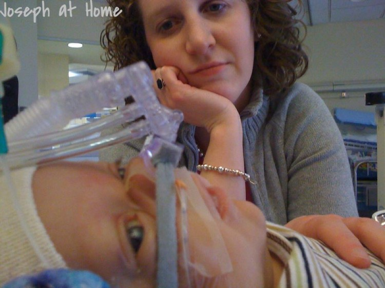 A woman looks at her child, who's hooked up to a breathing tube.