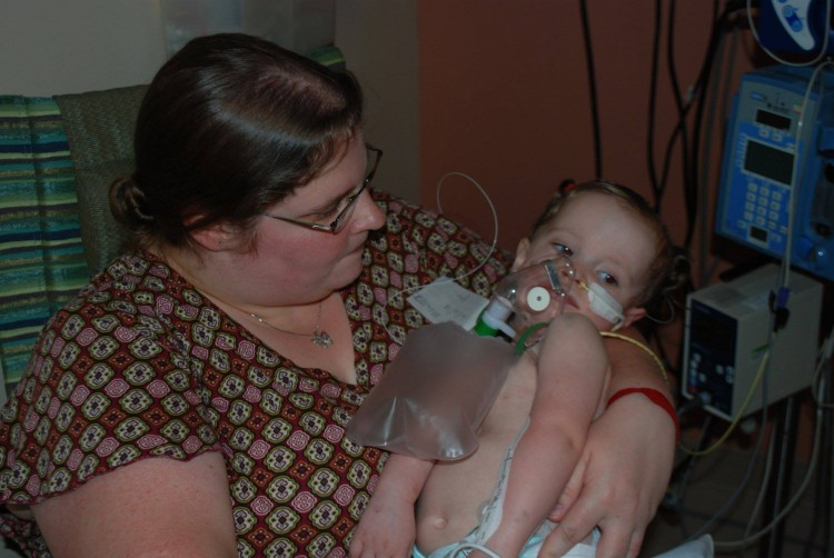 A mom holds a baby in a hospital.