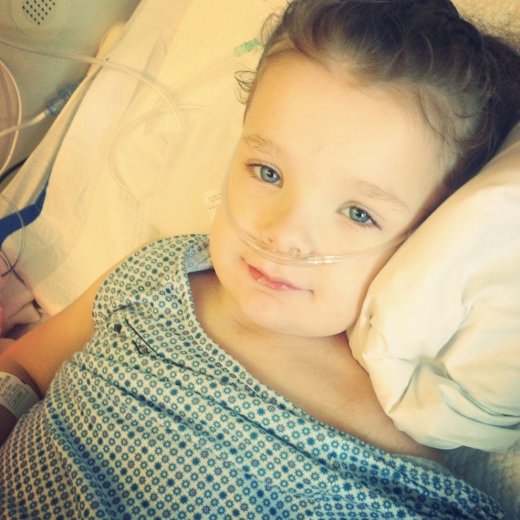 young child in hospital bed with oxygen tube