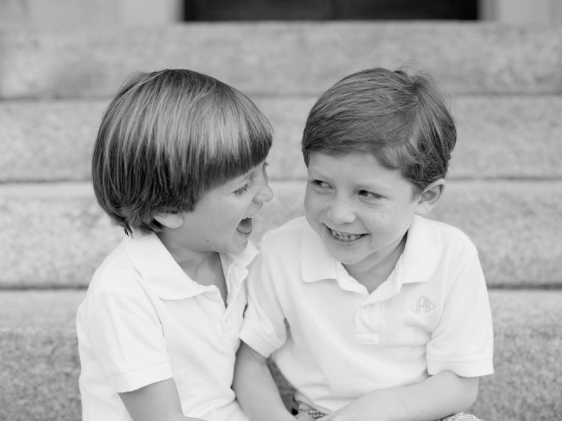 Black and white photo of the author's sons wearing white polo shirts, looking at each other and laughing