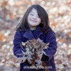 young girl poses outside wearing purple jacket and holding a handful of autumn leaves