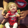 a baby girl sitting in her father's lap wearing a red onesie