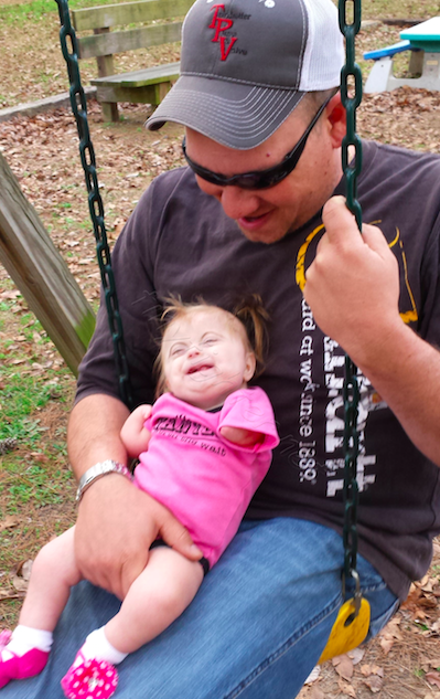 a small baby girl on her father's lap on a park swing