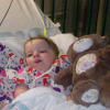 baby girl laying in a hospital bed next to a teddy bear