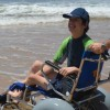 A boy in a wheelchair, wearing a hat, with someone helping push his chair by the ocean
