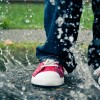 a boys red shoes in a puddle