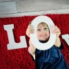 "A little girl sticking her head through a cut-out that says, ""LOVE,"" with her head in the ""O"""