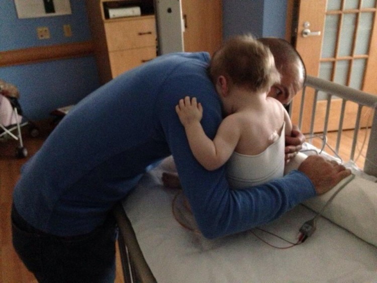 Dad hugging baby sitting on hospital bed
