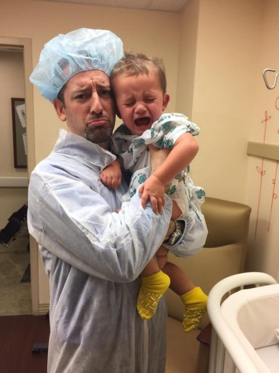 Dad making frowning face while holding crying baby in hospital